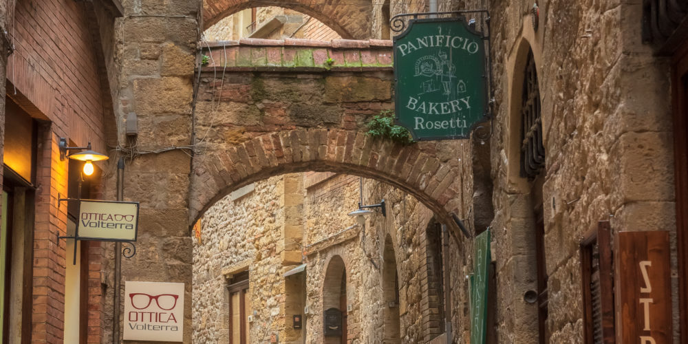 Volterra, Italy - April 10, 2019: Amazing view with a narrow picturesque medieval street of old town of Volterra in Tuscany, Italy